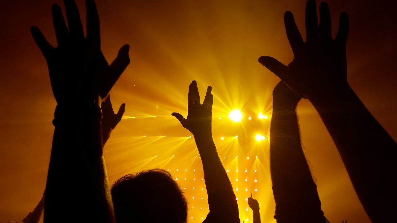 silhouette, human hand, real people, excitement, human body part, sunset, night, illuminated, outdoors, crowd, one person, sky, people