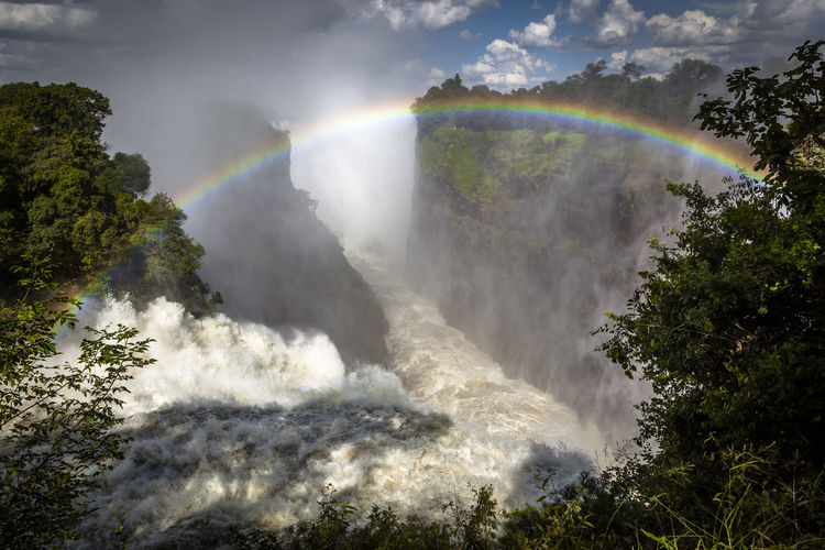 Scenic view of waterfall against rainbow in sky