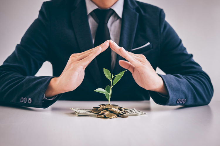 Midsection Of Businessman With Money And Plant On Table Against White Background