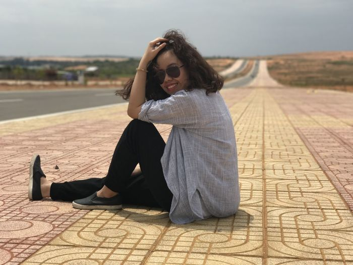 Portrait of young woman sitting on footpath