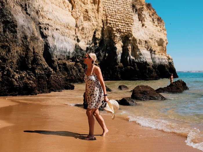 Woman Walking At Beach Against Cliff