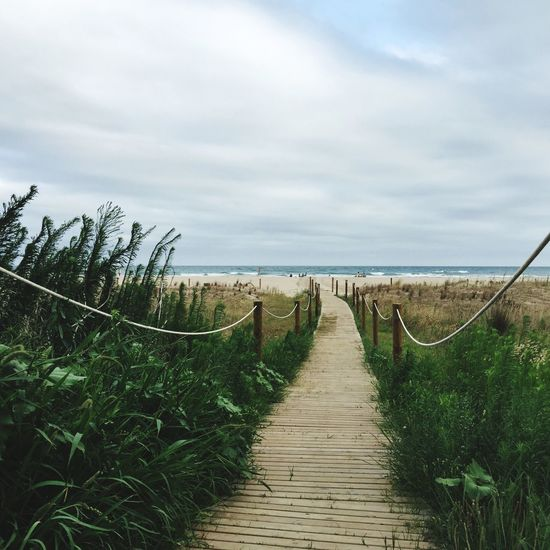 Narrow Pathway Leading To Calm Sea Against Clouds