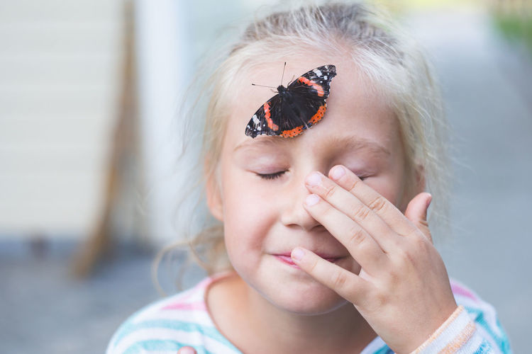 A beautiful black butterfly with orange spots, sits on a forehead of a caucasian girl of 7-8 years
