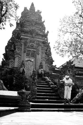 this is bali -- a balinese priest gives offerings at the saraswati temple in ubud Architecture B&w Street Photography Bali Bali, Indonesia Balinese Architecture Building Exterior Culture Day Façade Holy Man Kori Agung Low Angle View Man In White Monochrome Outdoors Place Of Worship Priest Pura Religion Spirituality Stairs Steps Temple - Building Temple Gate Ubud