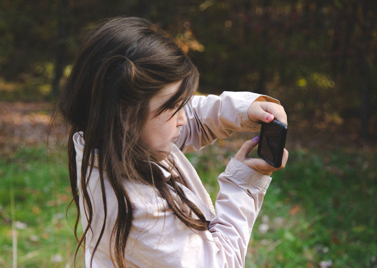 Close-up of cute girl photographing while standing in yard