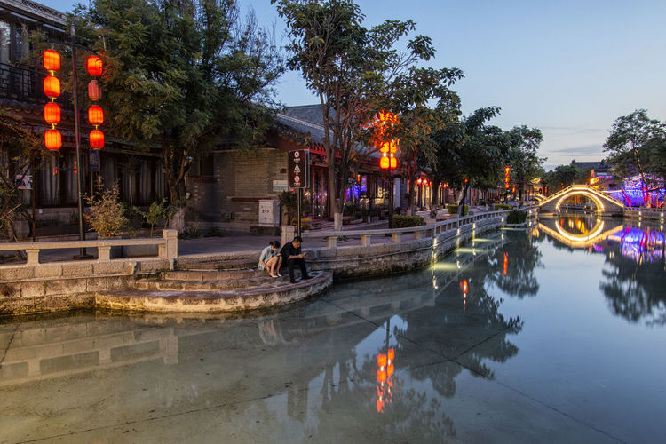 People on illuminated canal in city at dusk