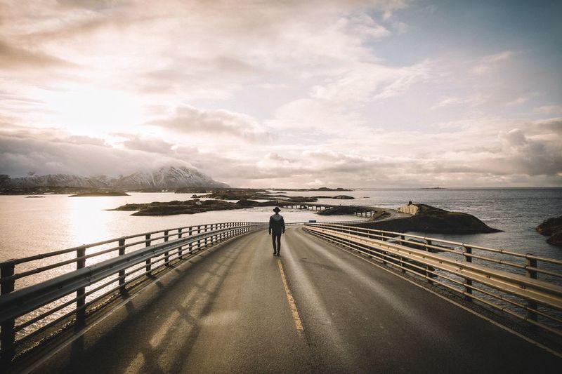 Rear view of man walking on atlantic ocean road against sky