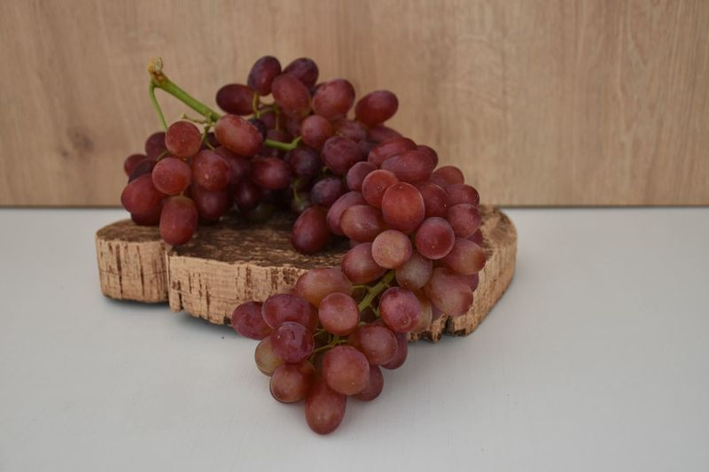 Food Food And Drink Freshness Healthy Eating Table Still Life Indoors  Wood - Material Fruit No People Close-up Grape Red High Angle View Brown Cutting Board Wooden Ripe