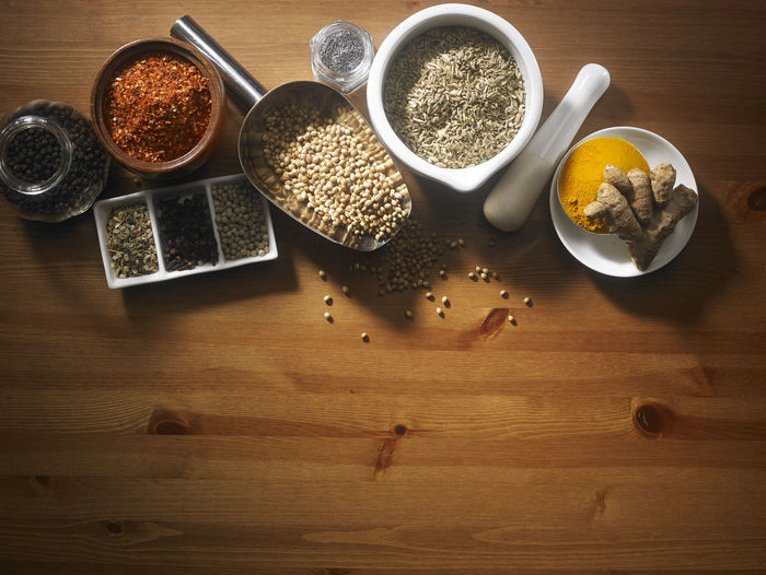 assorted spices on the wooden table Chili Pepper Food And Drink Herb Seed Spoon Wooden Table Aroma Assortment Brown Chili  Condiment Coriander Cumin Directly Above Food Group Of Objects Ingredient No People Paprika Pepper Scoop Shape Seasoning Spice Turmeric  Wood - Material