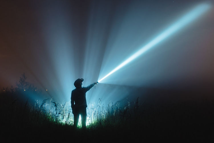 Man with illuminated flash light standing on field against sky at night