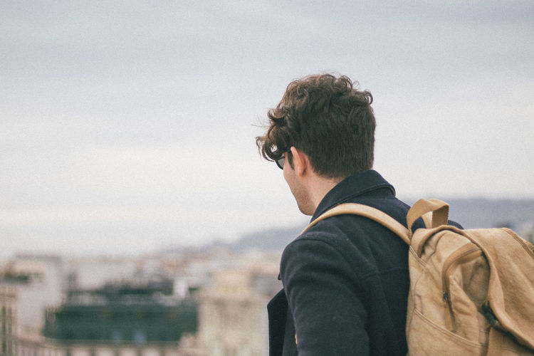 Man carrying backpack standing in city against sky