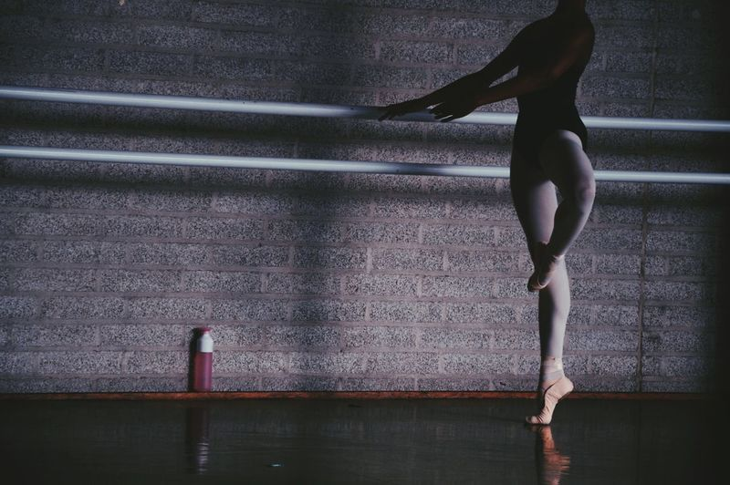 Low Section Of Young Woman Dancing On Floor At Ballet Studio