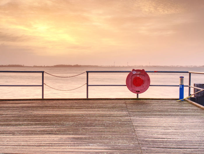 Red pier over sea against sky during sunset