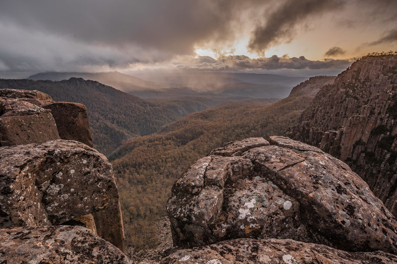 A snowstorm passes over towering dolerite cliffs at Devils Gullet to allow a brief shower of light to flood the view across the remote Tasmanian central plateau with its forests, valleys, mountains and rugged terrain. The storm engulfing Clumner Bluff (1559m) was directly overhead a few minutes earlier with white out conditions and summer snow. The dolerite columns in the foreground are over 220m high and plunge into the Fisher River valley which is part of the Tasmanian Wilderness World Heritage Area, on the northern rim of the Great Western Tiers. Tasmania, Australia. Australia Australian Landscape Australian Bushland Devils Gullet Fisher River Valley Great Western Tiers Isolated Rugged Cloud - Sky Clumner Bluff Dolerite Dolerite Columns Dramatic Sky Forest Landscape Mountain Mountain Range Outdoors Rock - Object Rugged Terrain Snowstorm Tasmania Tasmanian Wilderness World Heritage Area Wilderness Woods