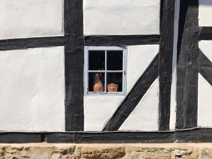 Window in historic timber framed black and white building wall
