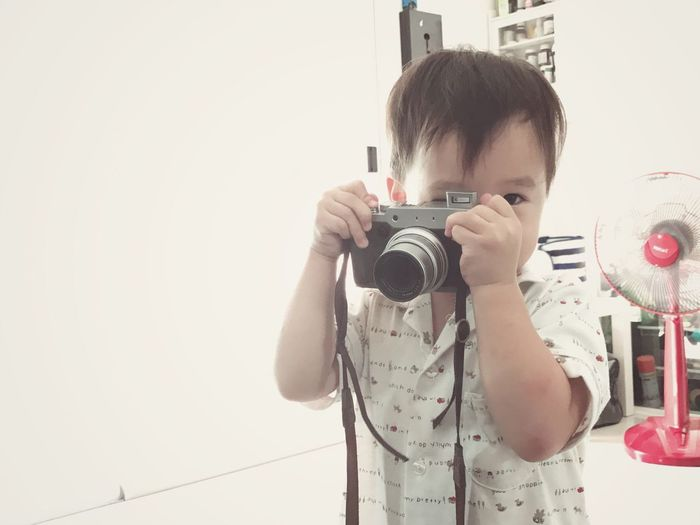 Portrait of baby boy photographing with camera at home