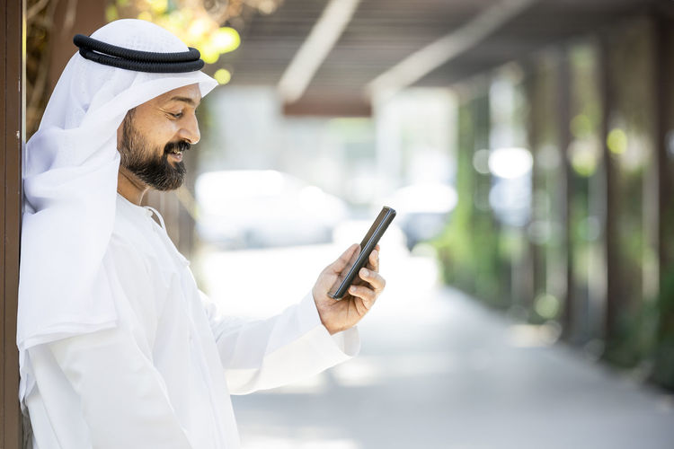 Smiling man using mobile phone while standing on street