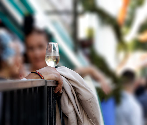 Cropped hand of person holding wineglass outdoors