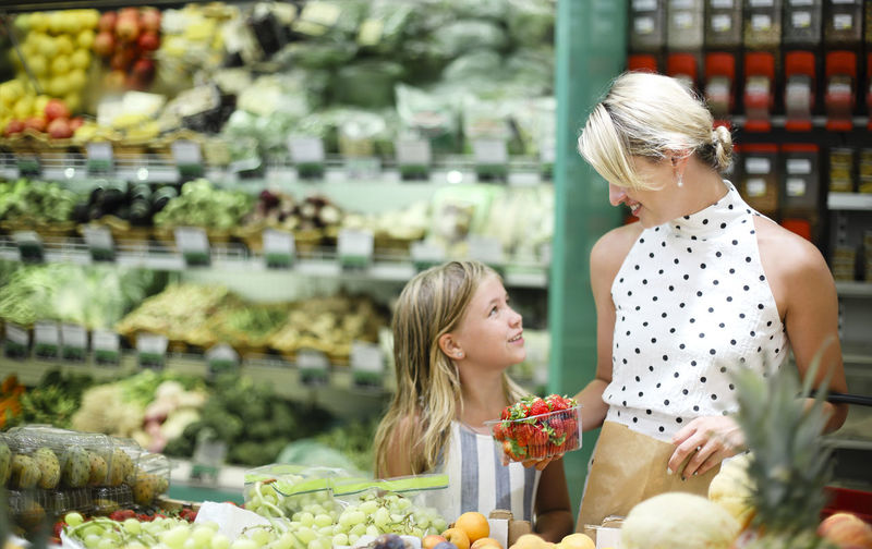 Smiling mother holding strawberry in supermarket