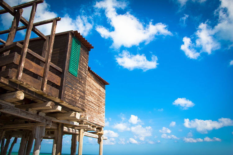 Low angle view of abandoned building against blue sky