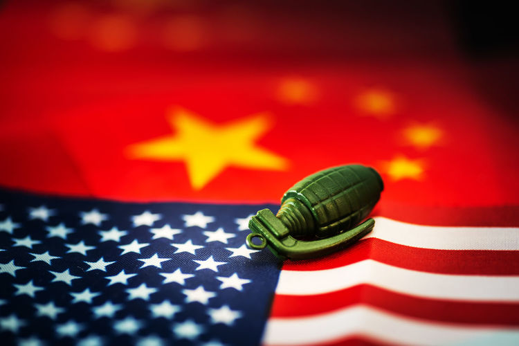 Close-up of grenade on american and chinese flag at table