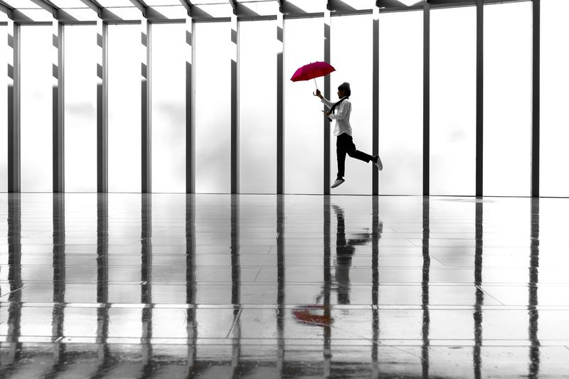 Side view of woman with umbrella standing in rain