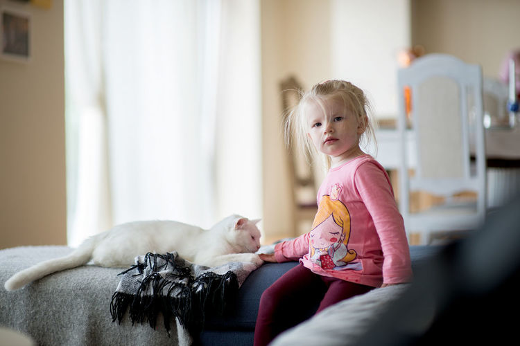 Beautiful portrait of blonde little girl with white cat EyeEm Best Shots Animal Themes Blond Hair Casual Clothing Child Childhood Cute Day Domestic Room Elementary Age Family Life Full Length Girls Happiness Home Interior Indoors  Lifestyles Mammal One Girl Only One Person People Real People Sitting Smiling White Cat