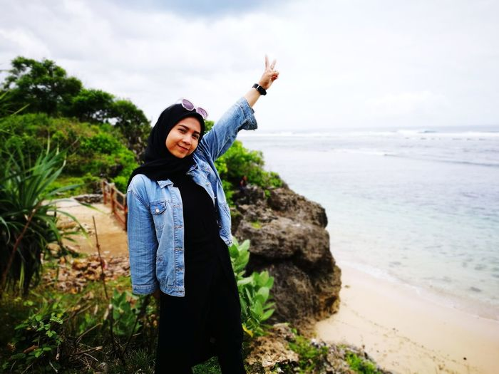 Portrait of young woman gesturing peace sign while standing at beach