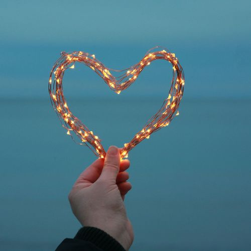 Close-up of hand holding illuminated heart shape