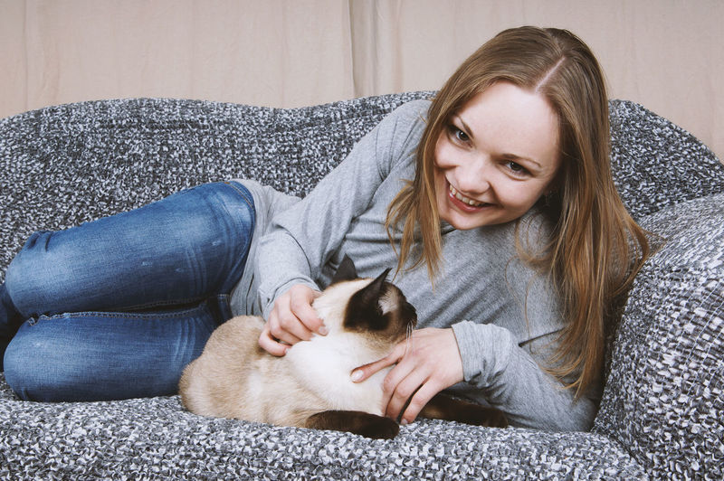 Couch Relaxing Stroking Casual Clothing Cat Cuddling Domestic Animals Domestic Cat Happiness Home Interior Indoors  Leisure Living Room Looking At Camera One Person Pets Real People Siamese Cat Smiling Sofa