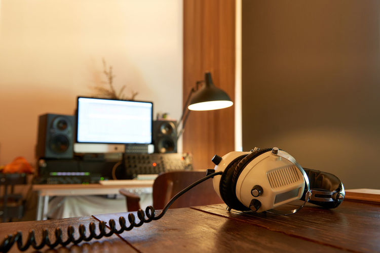 Microphone and headphone in home studio setup for sound engineer with soft shutter Headphones Home Studio Wireless Microphone Computer Cozy Desk Electric Lamp Focus On Foreground Home Interior Illuminated Indoors  Lighting Equipment Mixing Monitor Music No People Sound Recording Equipment Speaker Studio Shot Table Technology Warm Wood - Material Wooden