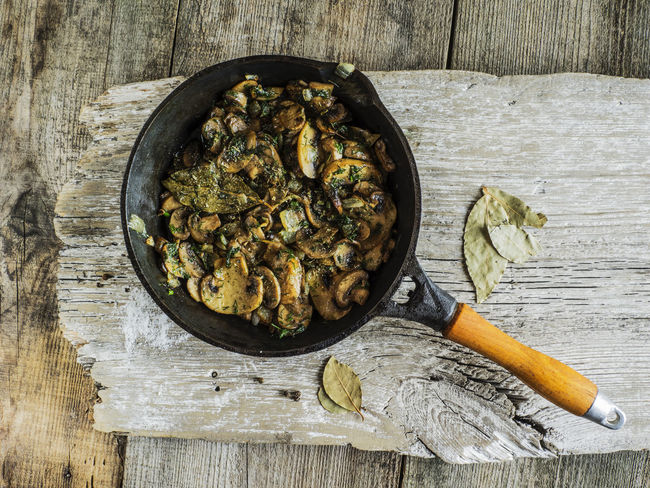 Fried mushrooms in a cast iron skillet on old weathering background Abundance Background Bowl Cast Iron Day Food Food And Drink Freshness Fried Healthy Eating Heap Large Group Of Objects Mushrooms No People Old Organic Skillet Table Vegetable Weathering Wooden