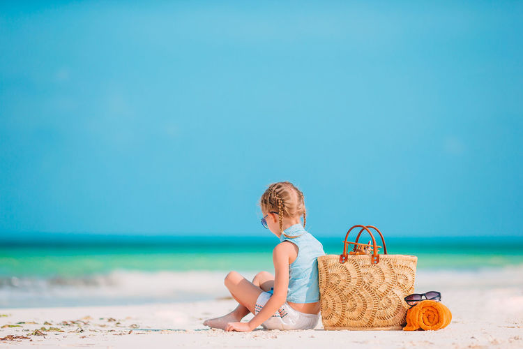Full length of girl sitting on beach against blue sky