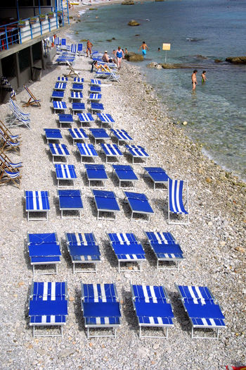 Rows of empty sunbeds on beach - Capri, Italy Bathing Beach Blue Sunbeds Capri, Italy Day Empty Sunbeds High Angle View Men Nature Outdoors Pebbles And Stones People Real People Sand Sea Sunbeds Water Let's Go. Together. Sommergefühle