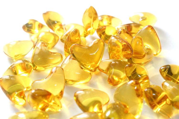 Close-up of heart shape capsules on white background