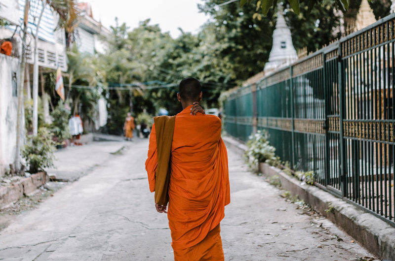 Rear view of monk walking on footpath