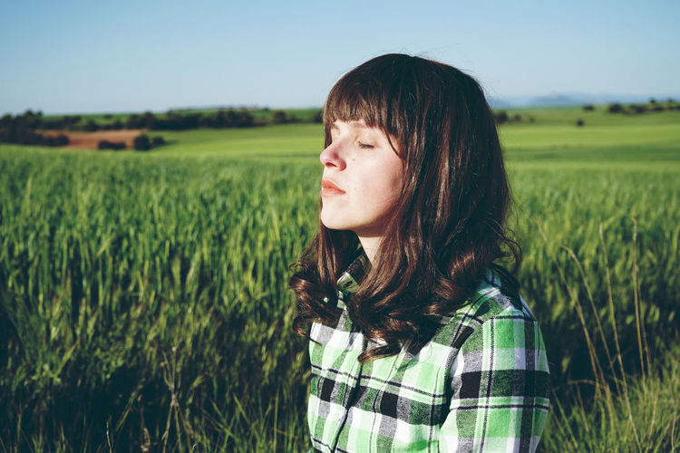 Woman With Eyes Closed Standing On Field During Sunny Day