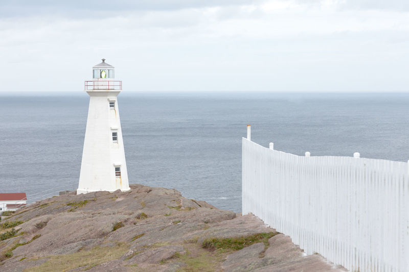 White fence and new functional lighthouse at Cape Spear Lighthouse National Historic Site, most Eastern place of Canada, Province of Newfoundland Labrador, NL, Canada, CD Cape Spear Cape Spear National Historic Site Cape Spear Newfoundland Lighthouse Lightstation St. John's, NL St. John's Canada Beacon Beautiful Place Travel Destination Architecture Built Structure Building Building Exterior No People Tower Security Protection Guidance Outdoors Direction Sea Water Horizon Over Water Horizon Tranquil Scene Safety