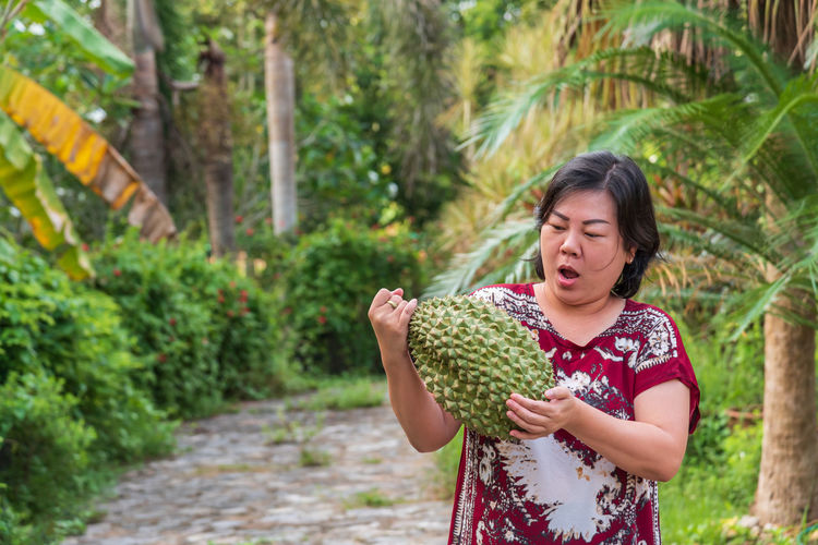 Shocked mature woman looking at durian while standing on footpath amidst plants