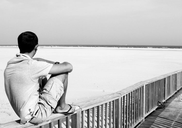 Rear View Of Man Sitting On Railing At Beach Against Sky