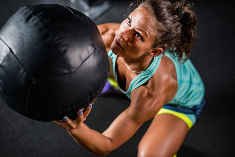 High Angle View Of Mid Adult Woman Exercising With Fitness Ball In Gym