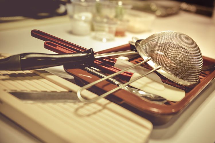 Close-up of kitchen utensils in tray on table