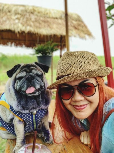 Portrait of woman in sunglasses with dog outdoors
