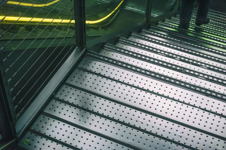 Man walking down metal staircase in Berlin, Germany Berlin Escalator Germany Horizontal Legs Metal Photography Reflections Shiny Unrecognizable Person Walking