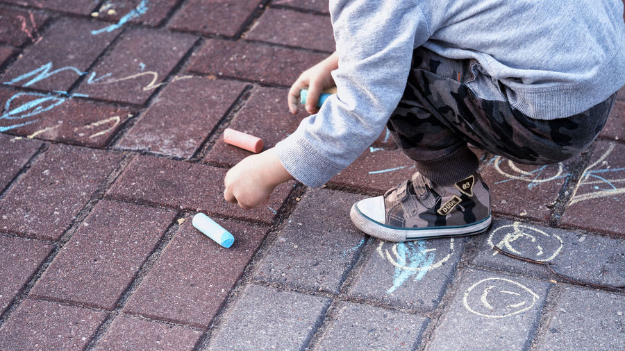 Crayons Body Part Casual Clothing Child Childhood City Human Body Part Human Leg One Person Outdoors Painting Painting Child Paving Stone Picture Real People Stone Street Street Photography