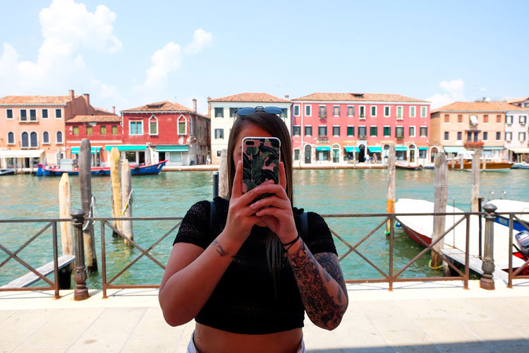 girl taking a photo on her mobile phone Venice Venice, Italy Italy City Travel Travel Destinations One Person Built Structure Real People Water Building Exterior Photography Themes Lifestyles Photographing Leisure Activity Standing Technology Front View Holding Casual Clothing Young Women Day Women Wireless Technology Outdoors
