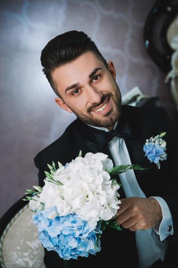 Portrait of confident bridegroom with bouquet