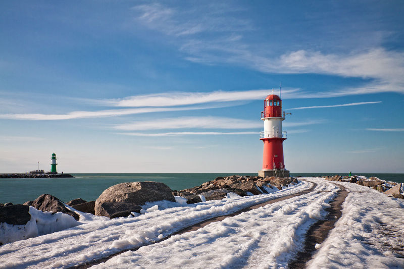 Snow Covered Pier Towards Lighthouse At Sea Against Blue Sky