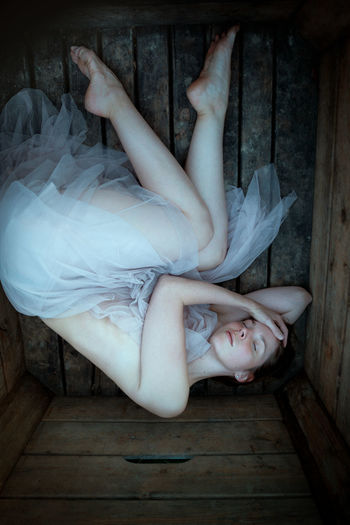 High angle view of woman lying down on wooden floor