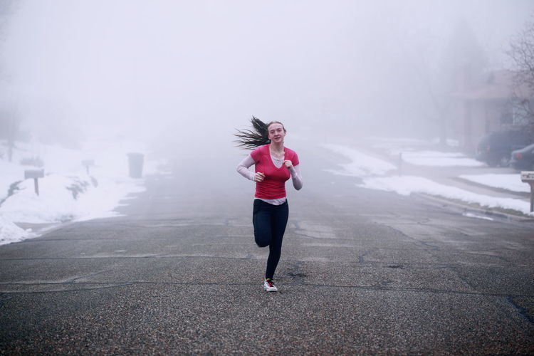 Portrait Of Smiling Young Woman Running On Road During Foggy Weather